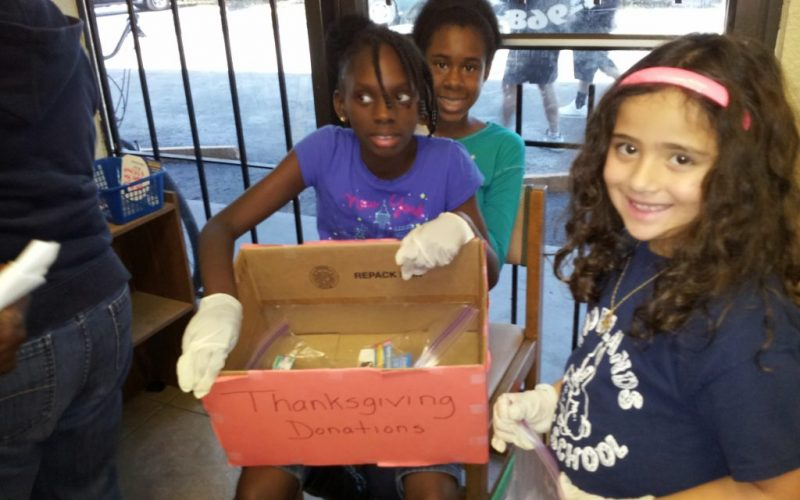 Children volunteer in a non profit organization prepares donations for the needy.