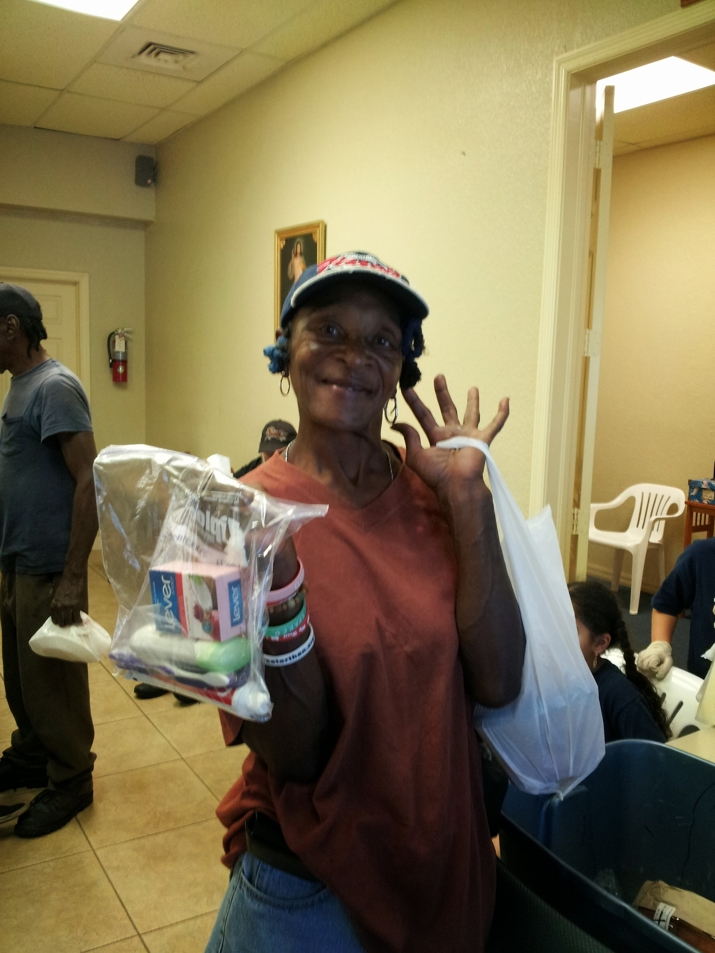 A woman receives a hygiene kit from non profit organization.