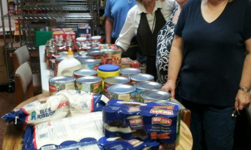 Soup kitchen volunteers showing the donated goods inside the storage room.