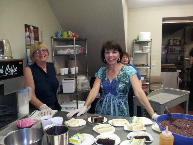 Homeless charity volunteer people preparing cakes for non profit organization event.