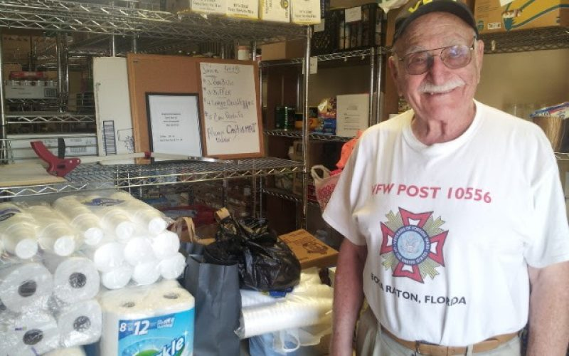 A happy old man takes a picture inside the soup kitchen storage room.