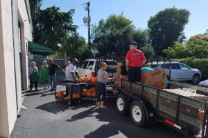 Homeless charity volunteer people unload a truck for a bunch of pumpkins.