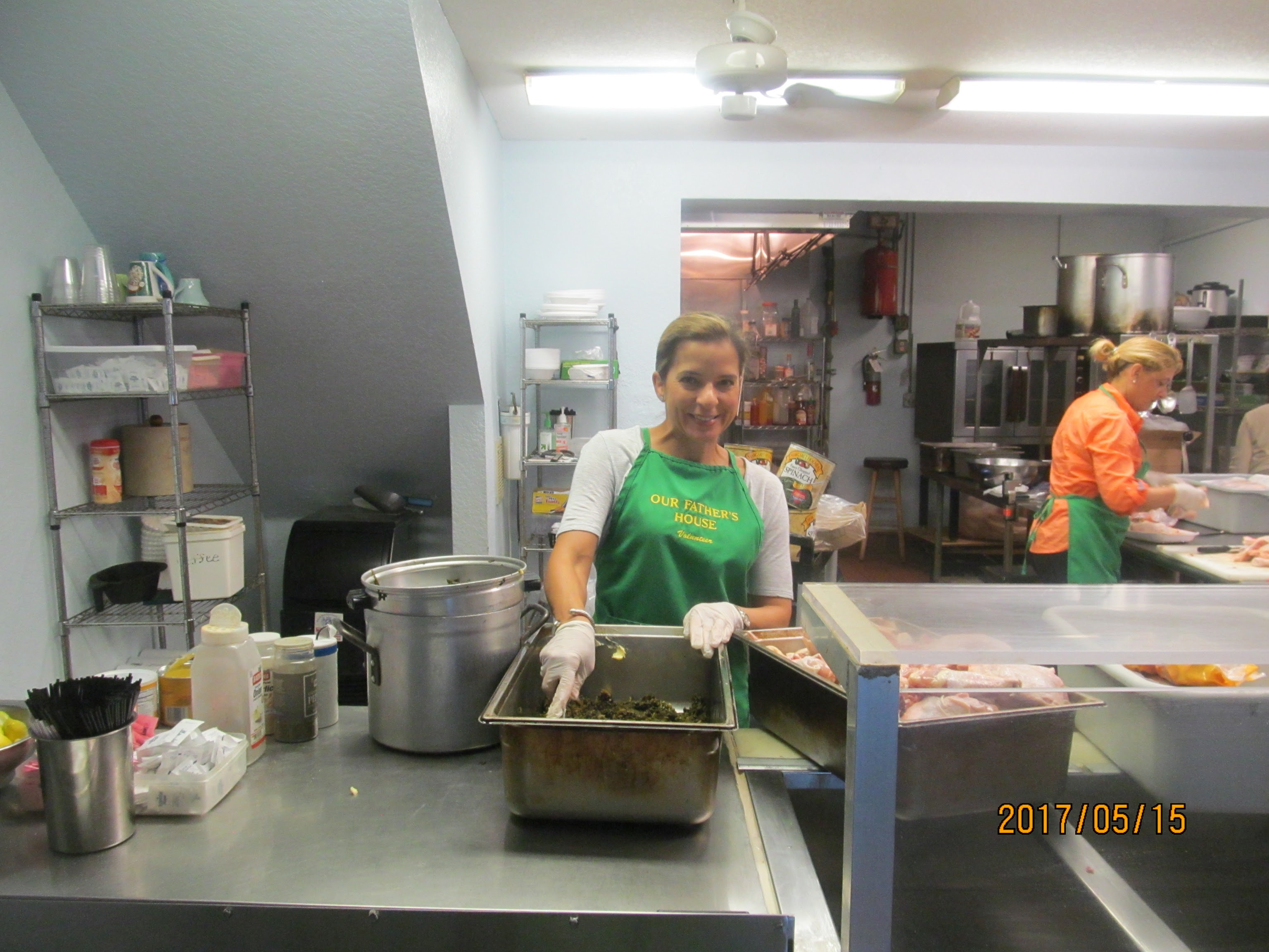 Soup kitchen volunteers staff preparing food for homeless people.