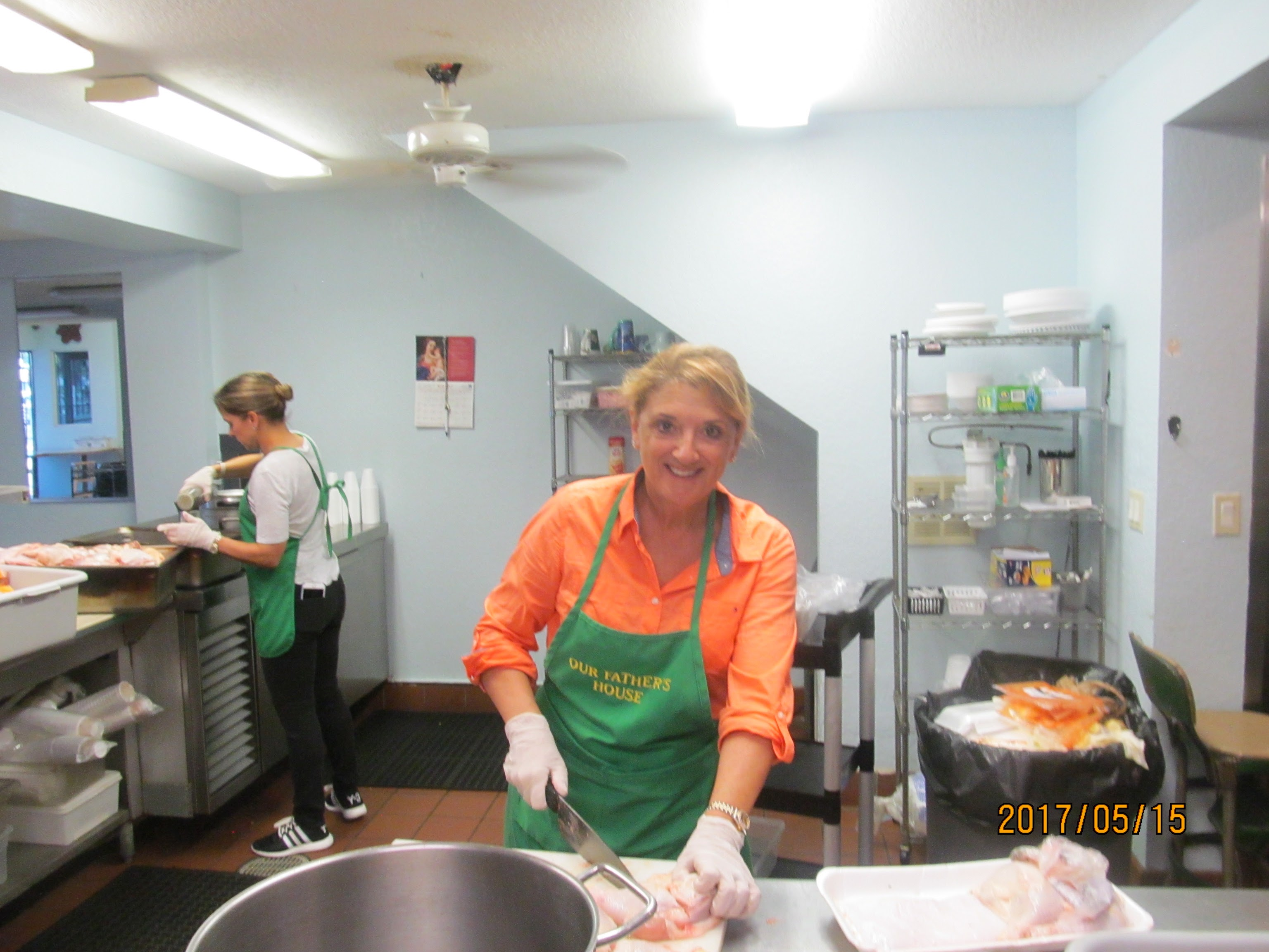 Soup kitchen volunteers staff cooking for homeless people.