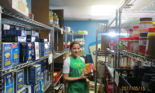 Soup kitchen volunteer takes a picture at a storage room.