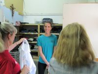 Members of non profit organization shows donated clothes.