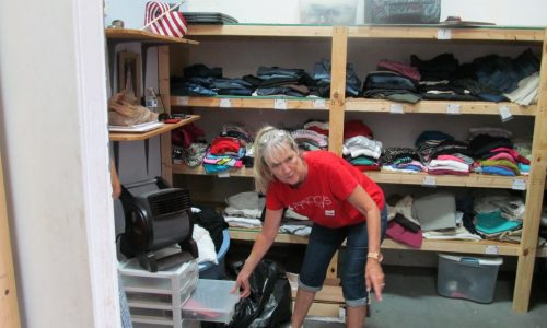 A member of non profit organization shows donated clothes.