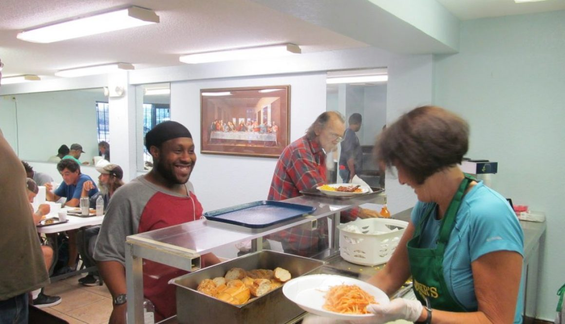 A homeless charity volunteer is enjoying serving food to the homeless people.