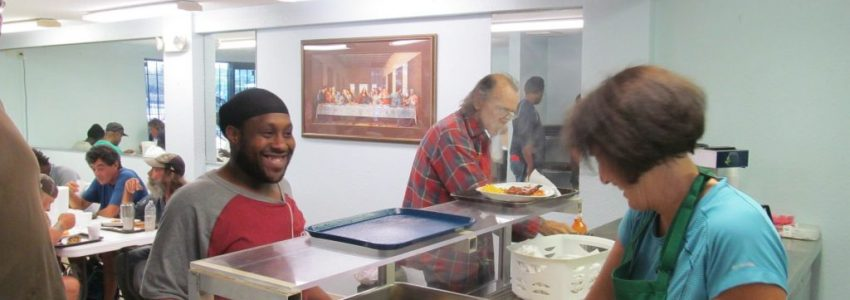 A homeless person getting free food at a soup kitchen.