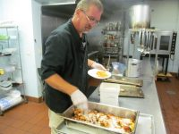 Soup kitchen volunteer chef prepares food f.or the homeless people
