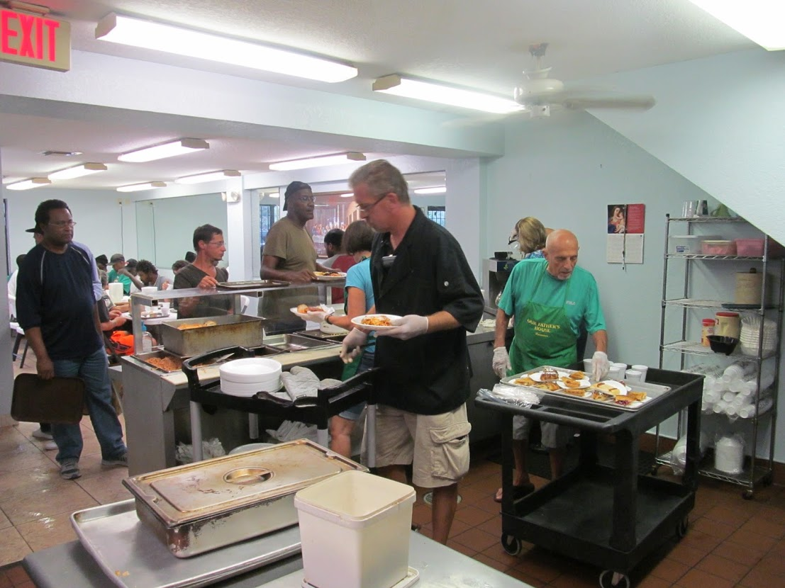 Homeless charity volunteers are serving food to the homeless people.