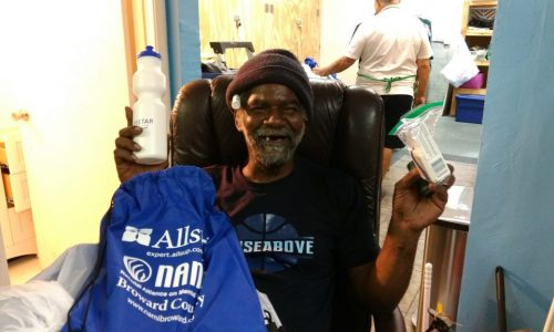 An old man receives a hygiene kit from non profit organization.