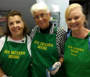 Soup kitchen volunteers take a picture while preparing food for the homeless people.