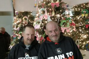 Two member of non profit organization stands in front of a Christmas tree.