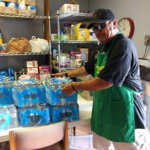 A soup kitchen volunteer serves dozen of bottled water for the poor.