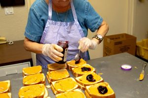 A homeless charity volunteer old woman makes sandwiches for feeding the homeless people.