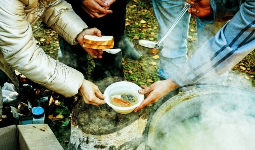 Someone giving soup and bread to a homeless person.