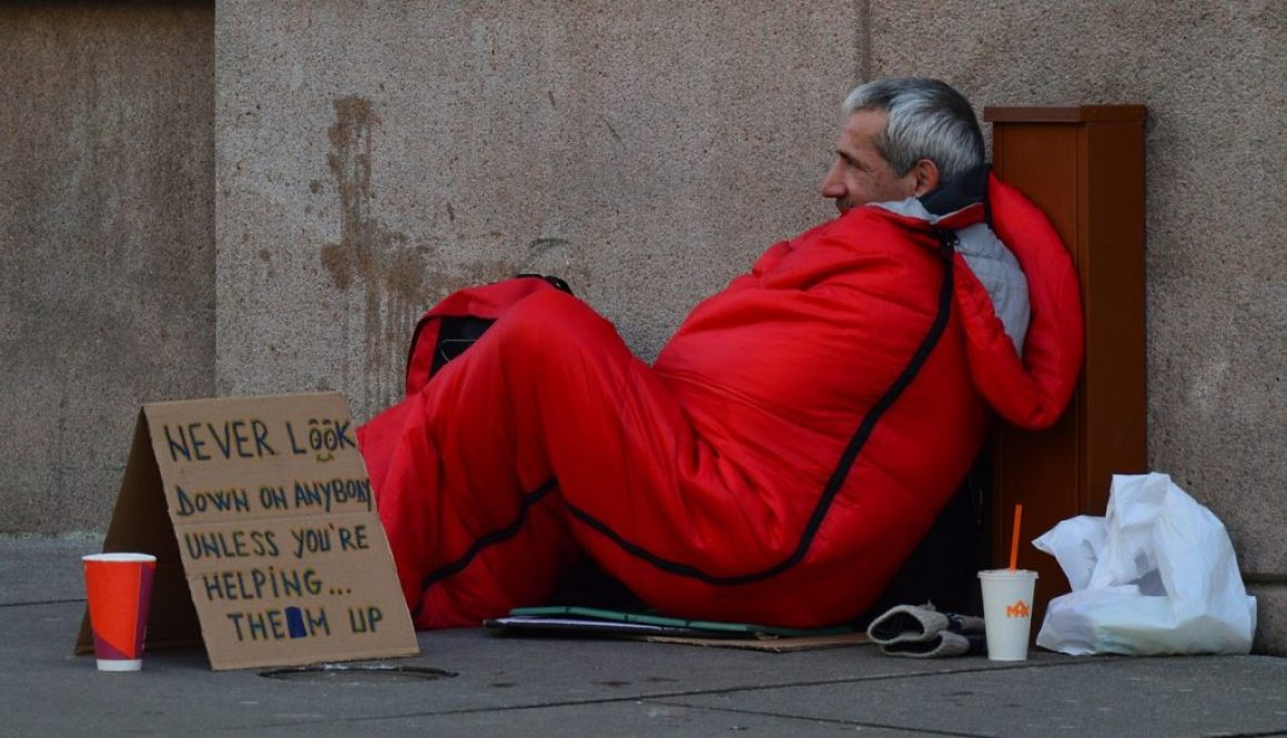 A homeless man in an orange sleeping bag in the streets of Florida.