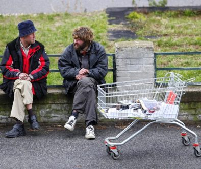 Two homeless men talking on the street.