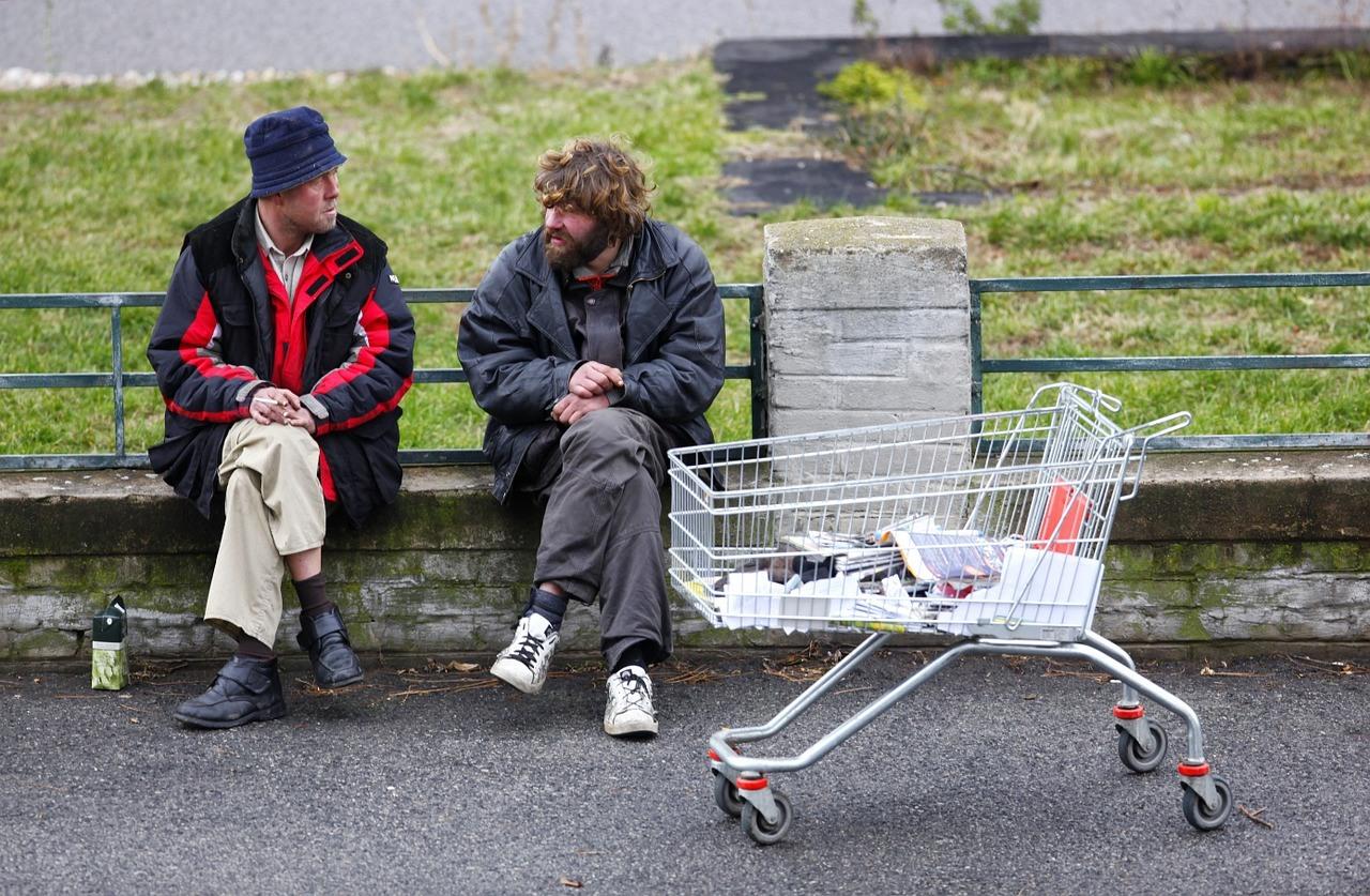 Two homeless men talking on the street.