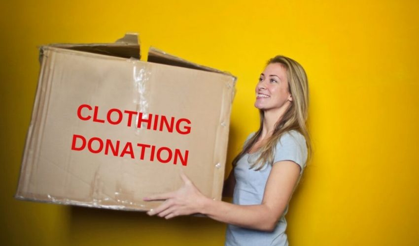 A woman carrying a box full of used clothing for donation.