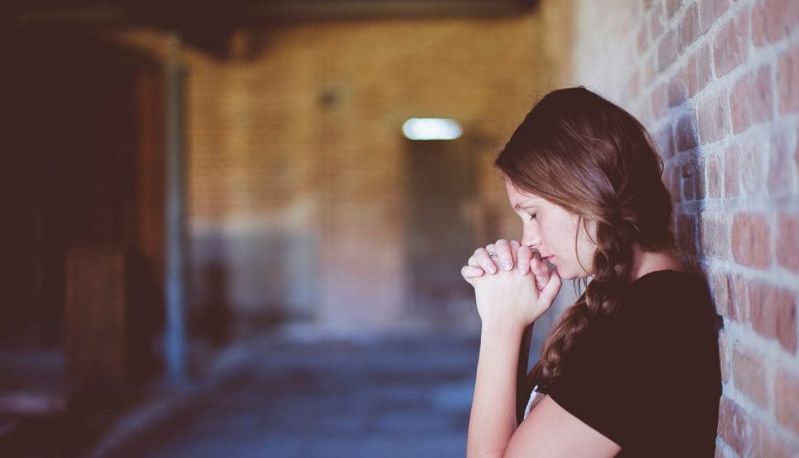 A girl sincerely praying for the homeless.