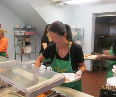A soup kitchen volunteer happily serving meals to the guests.