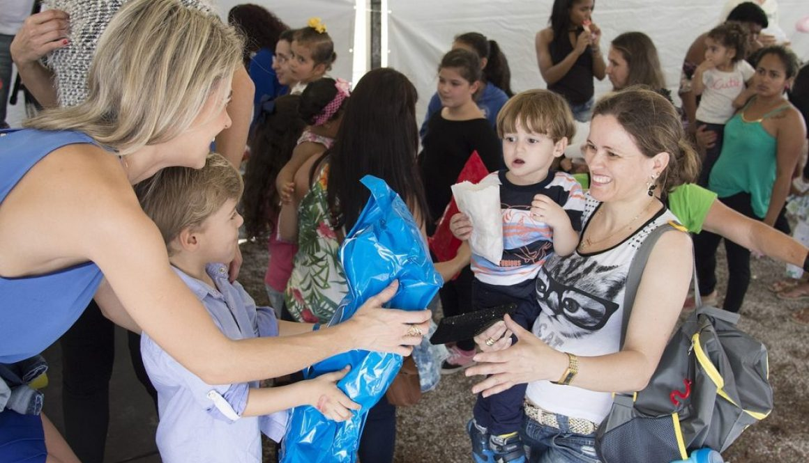 Mother and son giving care packs to a family who lost their home.