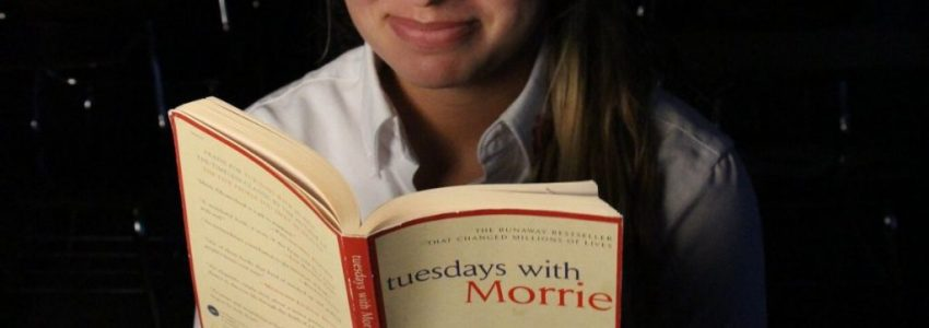 A woman reading Tuesdays with Morrie by Mitch Albom.