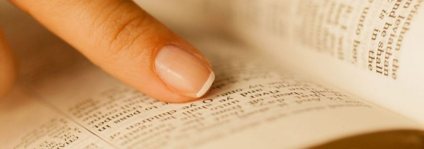 a person pointing at the definition of friendship written in the bible