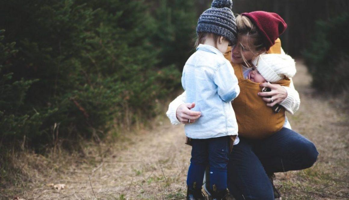 A homeless single mother hugging her children.