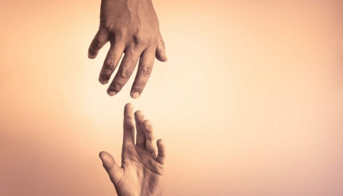 Two extended hands about to clasp each other symbolizing helping other people.