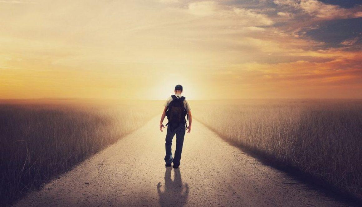 A man walking towards the sunrise.