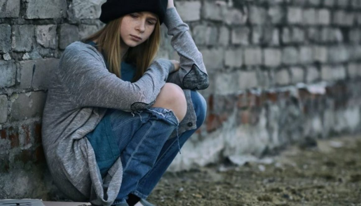 Homeless teenage girl sitting near brick wall outdoor got evected and no place to go.