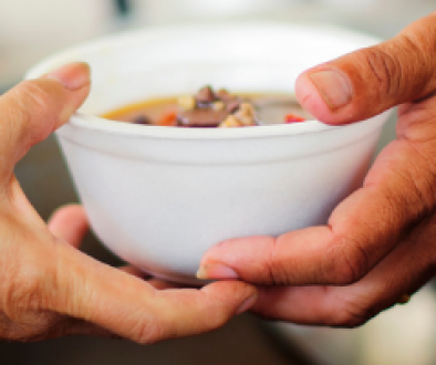 A picture of a hand that giving a soup to people during charity event