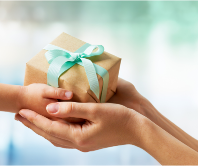 A loving mother giving poor child wrapped gift box