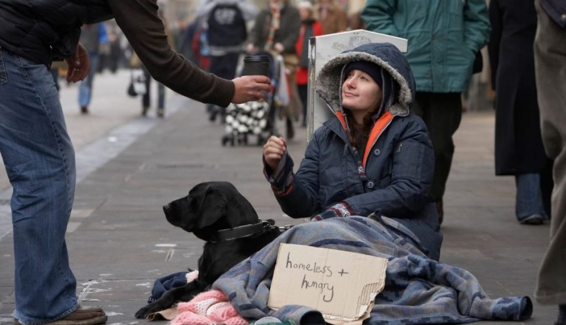 A homeless woman begs for money on a city street.
